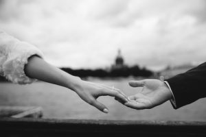closeup of male and female handtouching holding together on blurred background for love and healing concept. Black and white photo
